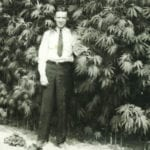 Black and white photo of a well-dressed man standing in front of a cannabis farm.