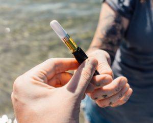 Woman with tattoos hands over an HVGC vape