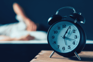 Alarm clock on bedside table in front of a blurred out image of a person in bed