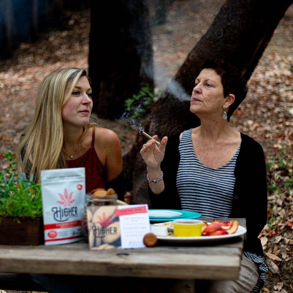 "Kirstie and ""Mama Donna"" sharing a joint in the mountains of Santa Cruz, where they live and operate Higher."